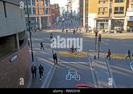Bicycle lane, cyclist on a bike on a pedestrian crossing and pedestrians in the street near the Barbican station City of London UK  KATHY DEWITT - Stock Image