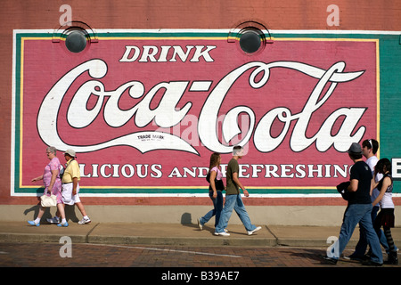 People walk past a vintage Coca Cola sign painted on the side of a building in downtown Rogers, Arkansas, U.S.A. - Stock Image