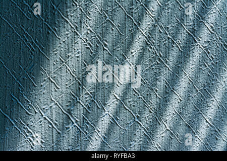 Pleasing texture detail of scratched stucco plaster. Interior close-up. Blue embossed wall lit by sunlight. Playful diagonal shadows. Retro background. - Stock Image