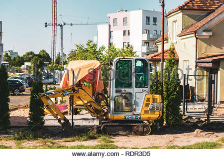 Poznan, Poland - July 20, 2018: Small excavator close by a construction area next to a modern apartment block on the Stare Zegrze district - Stock Image