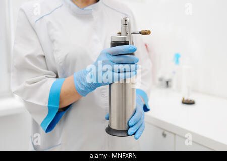 Doctor holding a special device for removing skin lesions - Stock Image
