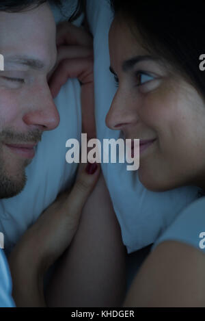 Couple lying in bed together - Stock Image