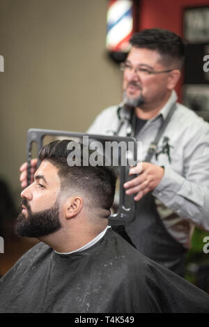 Handsome bearded man looking in the mirror after haircut, at barber shop . - Stock Image