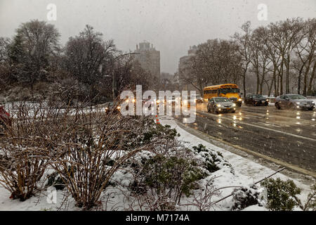 Brooklyn, USA. 7th March, 2018. Cars and school bus driving on slushy wet streets with wind driven snow during the - Stock Image