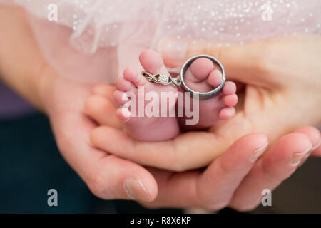 Wedding Rings on Newborn Baby Feet with Parents Hands Holding - Stock Image