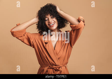 Smiling pretty african woman posing with closed eyes and holding her head over brown background - Stock Image