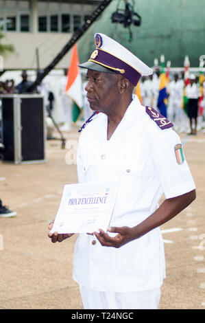 Abidjan, Ivory Coast - August 3, 2017: shoulder pad ceremony for students leaving the Maritime Academy. a standing major officer holds his diploma - Stock Image