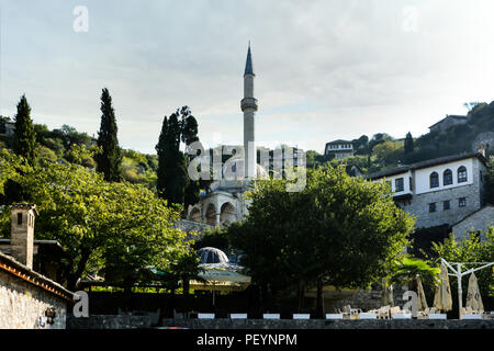 An ancient mosque and minaret looms over a narrow stone hillside pathway in the medieval city of Pocitelj Capljina in Bosnia and Herzegovina - Stock Image