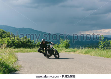 Young male motorcyclist on vintage motorcycle swerving around rural road bend, Florence, Tuscany, Italy - Stock Image