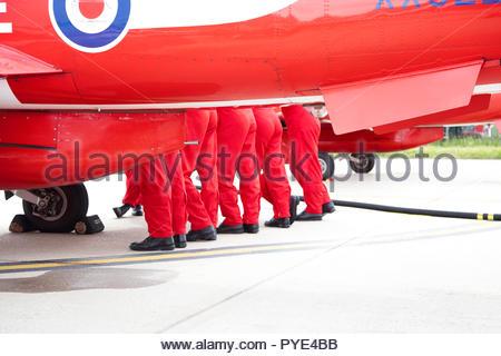 Legs of people standing by Red Arrows airplane on RAF Scrampton, UK - Stock Image