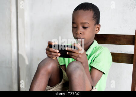 A child sitting on a chair is playing games in a mobile phone. - Stock Image