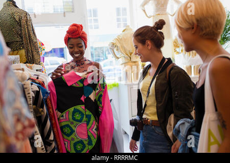 Young woman friends shopping in clothing store - Stock Image