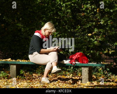 Lady woman enjoying reading book newspaper sms in warm sun Germany Europe - Stock Image