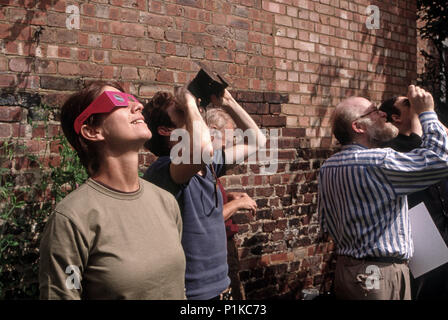 Watching a solar eclipse in Islington London using protective eye wear - Stock Image