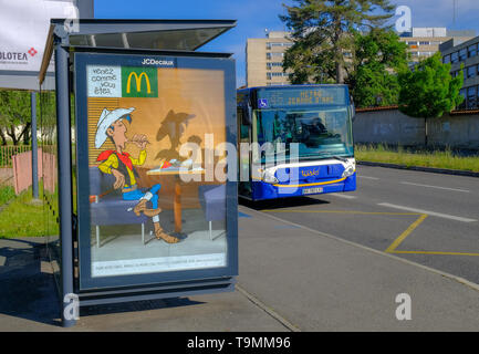 Local city bus stopping at shelter with McDonald's advertising featuring Lucky Luke, stating 'Venez comme vous êtes ' (tr. Come as you are) Toulouse - Stock Image