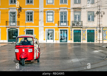 A three-wheel tuk tuk tourist taxi parked in a square of Baixa district, Lisbon, Portugal - Stock Image