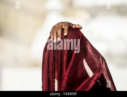A young novice monk prays beneath his red robes infront of the Shwedagon Pagoda, Myanmar. - Stock Image