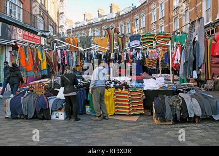 A market trader man selling mens clothing in Brixton street market scene Electric Avenue Brixton South London England UK   KATHY DEWITT - Stock Image