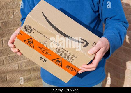 Man holding Amazon prime video box England UK United Kingdom GB Great Britain - Stock Image