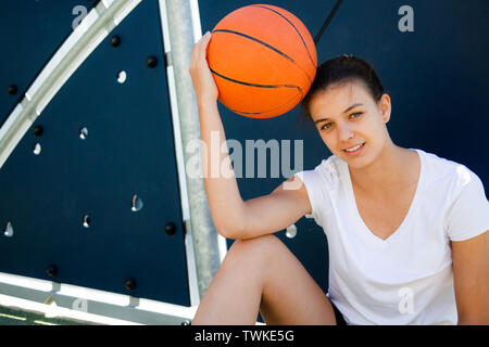 Beautiful female basket player resting on the floor with ball on head - Stock Image