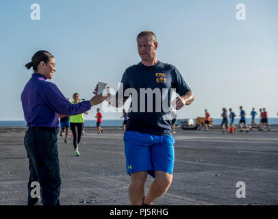 180826-N-FA806-0068 ATLANTIC OCEAN (Aug. 26, 2018) Aviation Boatswain's Mate (Fuels) Airman Andrea Franco, left, from San Diego, hands water to Chief Aviation Support Equipment Technician Joey Lewis, from Scranton, Pennsylvania, during a 5k fun run on the flight deck aboard the aircraft carrier USS George H.W. Bush (CVN 77). The ship is underway conducting routine training exercises to maintain carrier readiness. (U.S. Navy photo by Mass Communication Specialist 3rd Class Roland John) - Stock Image