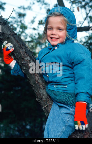 Happy SevenYear Old Girl Smiles While Climbing a Tree, USA - Stock Image