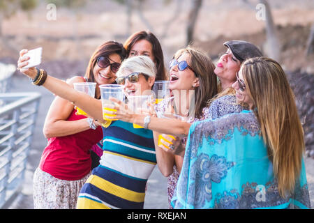 Group of happy and cheerful caucasian young women toasting and clinking with plastic glasses and taking a selfie picture in friendship and having fun  - Stock Image