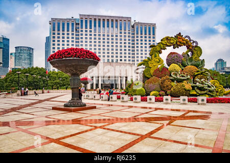 2 December 2018: Shanghai, China - People's Square and the People's Government Building, Shanghai, with a large and impressive topiary. - Stock Image