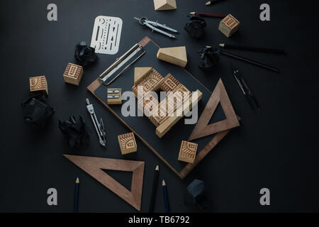 Constructing a house, real estate planning and studying architecture concept. Dark header with toy wooden blocks, small house, pencils and copy space. - Stock Image