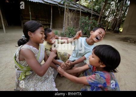 BANGLADESH Children of the Garo tribal minority playing in the yard of their farmhouse, Haluaghat, Mymensingh region photo by Sean Sprague - Stock Image