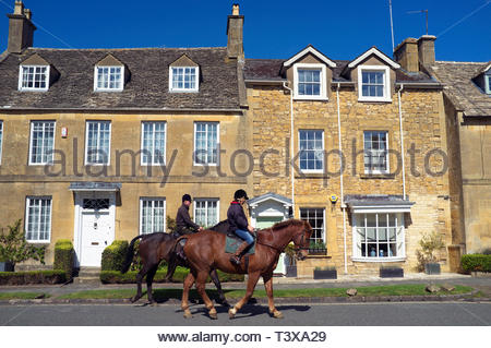 Horse riders trot by in the Cotswold village of Broadway in Worcestershire, UK. - Stock Image