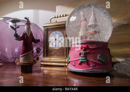 A side table with Christmas decorations and a snow globe - Stock Image