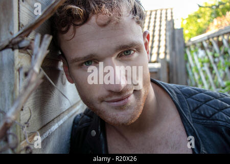 Good looking man with ginger stubble and open jacket looking at camera - Stock Image