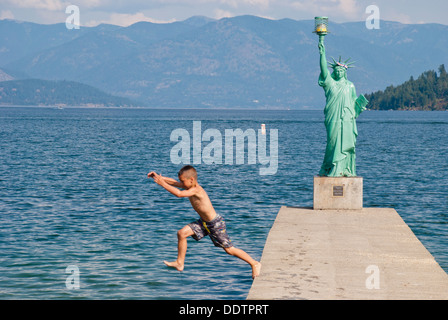 A young boy braves the chilly waters of Lake Pend Oreille, Sandpoint, Idaho, USA. - Stock Image