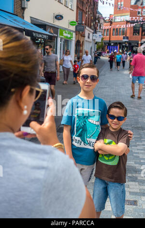 A mum takes a photograph of her young sons using her mobile phone. - Stock Image