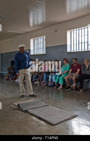 Tourists listen to a former prisoner, now a tour guide, in a communal cell at Robben Island, where Nelson Mandela was imprisoned during apartheid, Cap - Stock Image