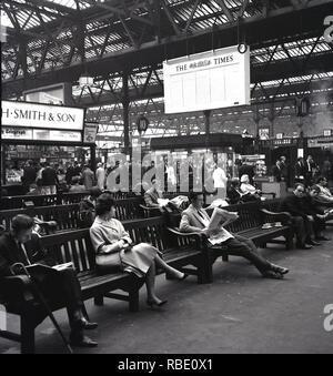 1950s, London, rail passengers waiting for their train, Waterloo, London, England, UK - Stock Image