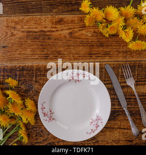 Plate and decor of flowers on the background of vintage wooden planks. Vintage background with dandelion flowers and place under the text. View from a - Stock Image