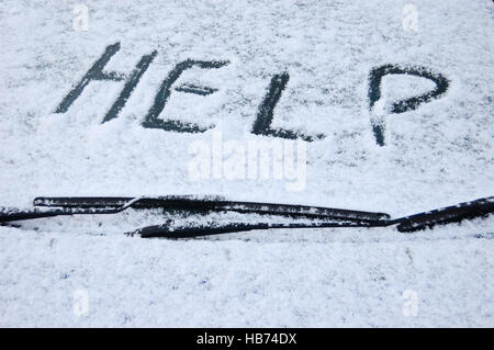 Snow covered car windscreen with the word help written in the snow - Stock Image