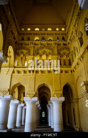 Columns and arches in one of the corridors surrounding main courtyard of 17th-century Thirumalai Nayak Palace, Madurai, Tamil Nadu, India. - Stock Image