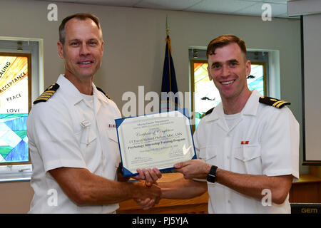180828-N-IY469-025 – Capt. Devin Morrison, NMCP acting executive officer, presents Lt. David Phillips with his graduation certificate. Phillips will be stationed at Great Lakes, Illinois. - Stock Image