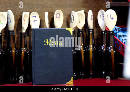 A menu with numbered wooden spoons behind. The spoons are in beer bottles - Stock Image
