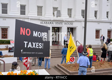 People listen to a speaker protesting taxes or a gas tax with signs against more taxes at the Alabama State House in Montgomery Alabama, USA. - Stock Image