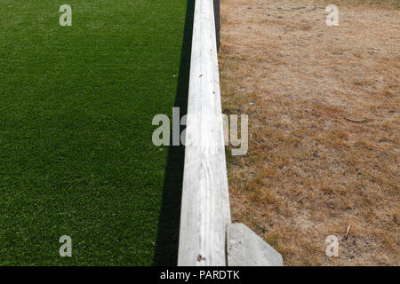 Artificial grass on the left and dry grass during very hot weather either side of a low fence. - Stock Image