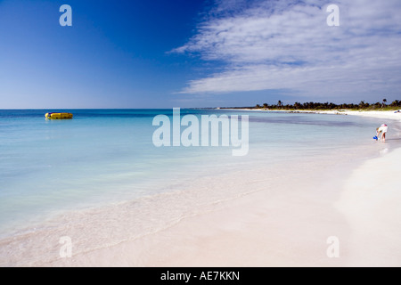 Beautiful beach and blue sea at Dreams Tulum, Tulum, Quintana Roo, Mexico with young girl bending over to pick up - Stock Image