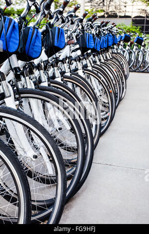 Bike rentals in a row at an outdoor bicycle rental business - Stock Image