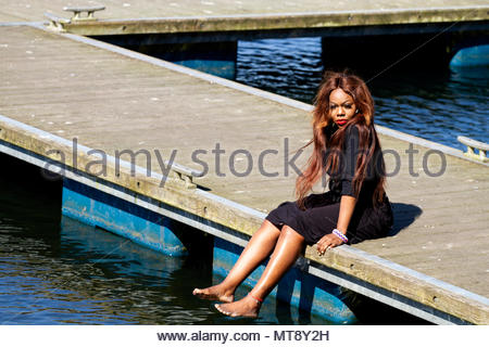 Dundee, Tayside, Scotland, UK. 28th May, 2018. UK weather: Heatwave sweeping across North East Scotland with temperatures reaching 23ºC. A young West African woman with long hair enjoying the glorious sunshine sitting on the jetty at Clatto Country Park in Dundee, UK. Credits: Dundee Photographics / Alamy Live News - Stock Image