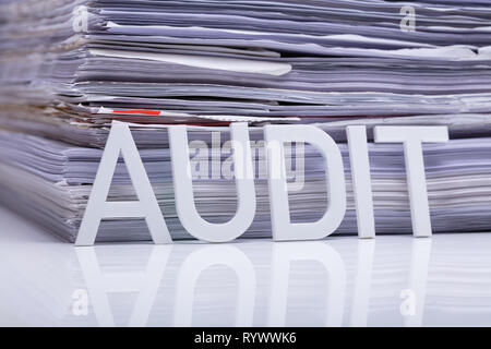 Close-up Of Audit Word And Stacked Document On Reflective Desk - Stock Image