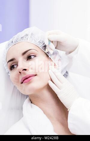 Dermatologist applying thread applicator on woman's face, close-up. - Stock Image