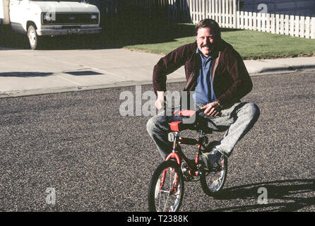 1993, Middle Aged Dad Rides His Child's Bike, USA - Stock Image